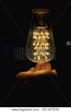 Light bulb with hand Hand under light bulb vintage light bulbs in dark time of the day warming up hands