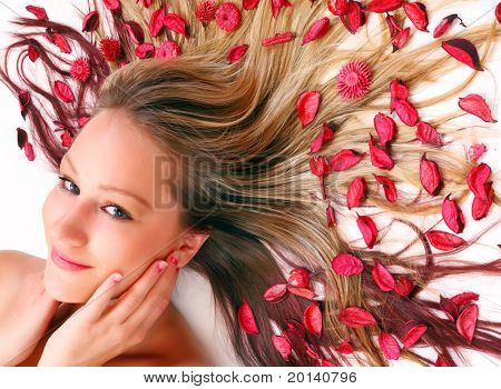 Beautiful young woman with flowers on her long hair.