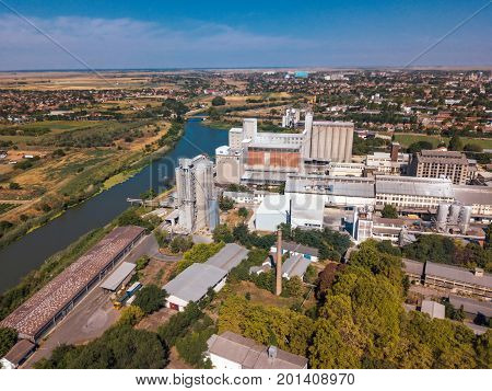 Drone pov aerial view of industrial cityscape with factory buildings and warehouses by the river