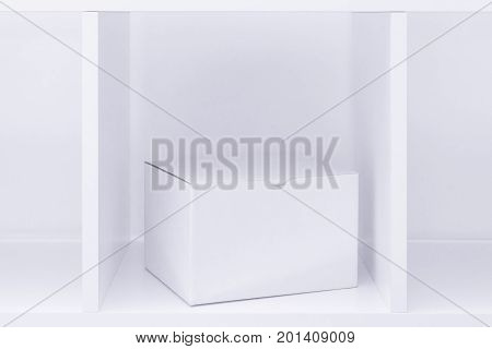 White cardboard box on wooden shelf as copy space useful for package design mock up or postal mail and package delivery service background