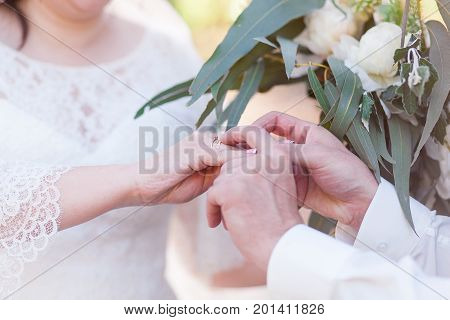 He Put the Wedding Ring on Her. Bouquet on background. Close-up shot
