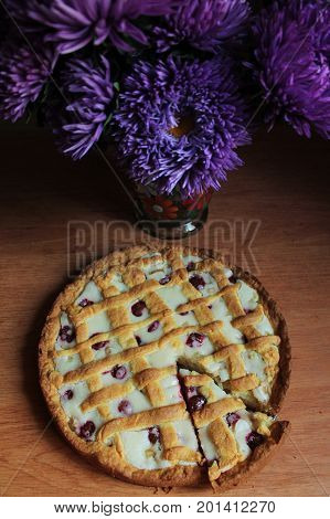 A bouquet of flowers next to a homemade pie with rhubarb and raspberries