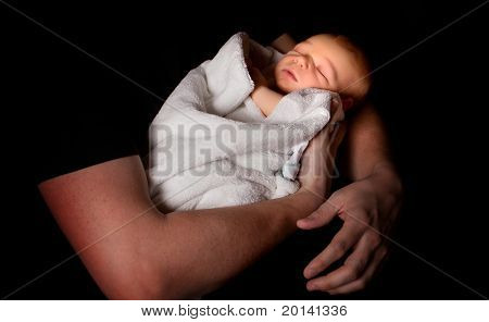 Father holding his baby with light falling on the face of the sleeping baby (16 days old)