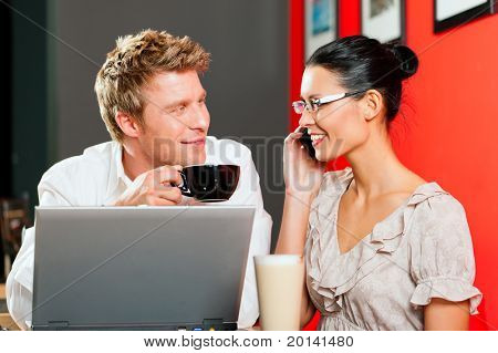 Couple in coffeeshop with laptop and mobile; obviously they are working