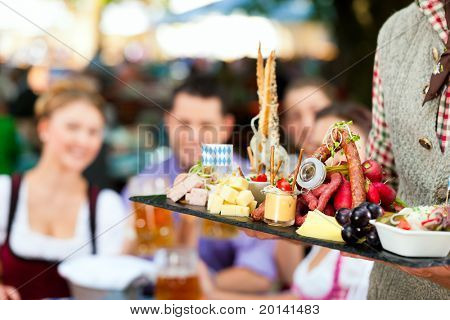 In Beer garden in Bavaria, Germany - beer and snacks are served; focus on meal