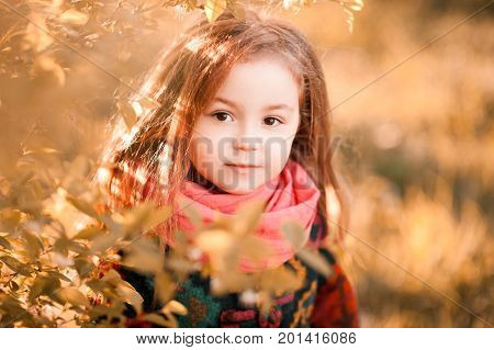 Blonde stylish kid girl 3-4 year old wearing scarf and jacket posing outdoors. Looking at camera. Childhood. Autumn season.