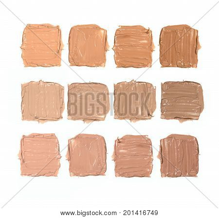 Three rows of four samples of neutral, cold and warm shades of foundation on white background