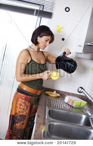 Modern woman preparing tea at the kitchen (selective focus with shallow DOF)