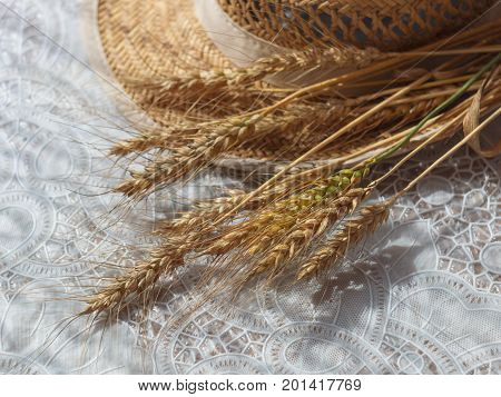 wheat spikelets and wicker straw hat on white table. selective focus