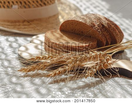 sliced bread with wheat spikelets on wooden chopping board and blurred straw hat on background. selective focus
