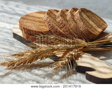 bread slices and wheat spikelets on wooden chopping board. selective focus