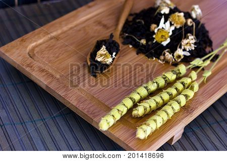 Black friable tea with the sage salvia and chamomile. On wooden spoon on tray