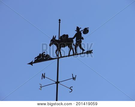 Wind vane of mule and prospector	blue sky