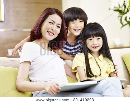 asian mother and two children sitting on couch reading a book.