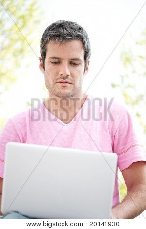 Handsome man with laptop outdoors