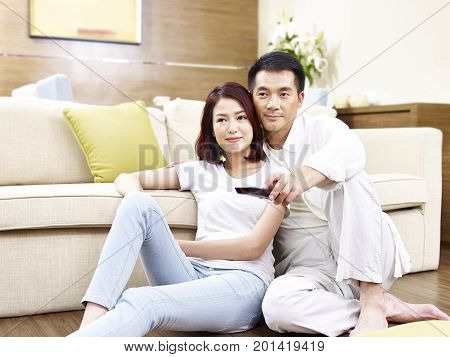 asian couple sitting on floor watching TV together.