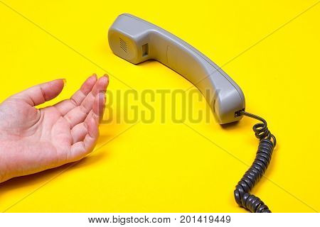 female hand lies next to the telephone receiver on the wire on a yellow background