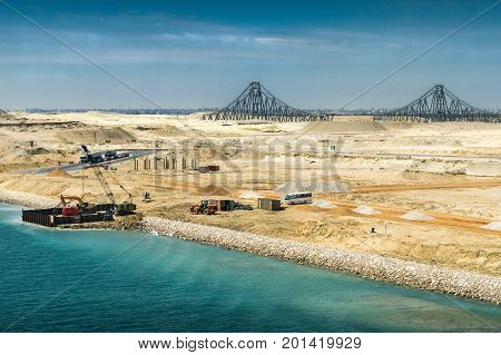 View from the newly opened extension channel of the Suez Canal to the El Ferdan Bridge and the remaining construction works on the canal in the foreground