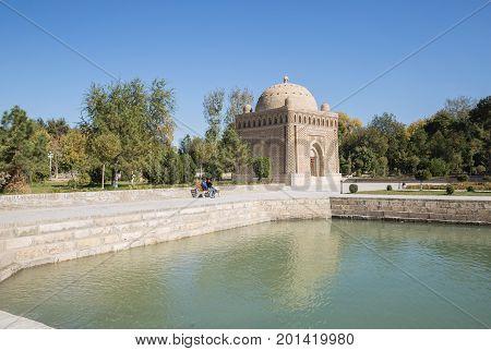 BUKHARA UZBEKISTAN - OCTOBER 19 2016: Unidentified people are sitting on a park bench near the Samanid mausoleum