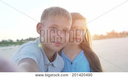 Little boy and girl of 8 - 10 years old making selfie using smartphone. Kids on vacation or holidays in summer.
