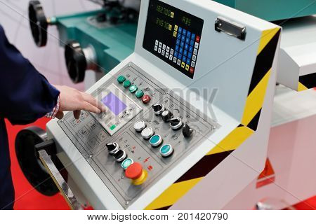 Operator working with control panel of cnc turning and milling machine. Selective focus.