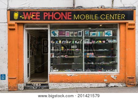 Galway Ireland - August 3 2017: Small business facade of shop selling mobile phone technology and accessories on side street. Peeled orange front with open door and display window.