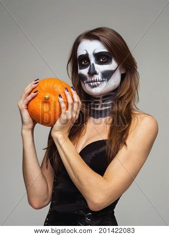 Portrait of young beautiful girl with fearful halloween skeleton makeup holding pumpkin over gray background.