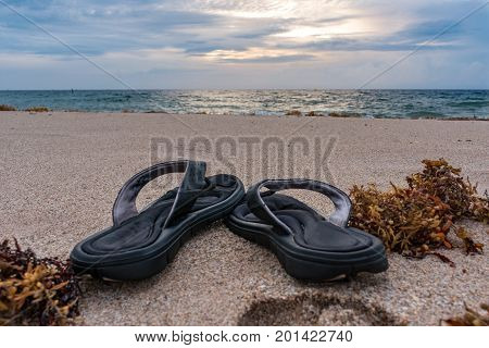 sandals in the sand on a cloudy morning at the beach