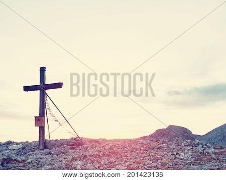 Modest Wooden Cross Raised On Rocky Alpine Mountain Summit . Sharp Rocky Peak. Gentle Clouds  In Blu