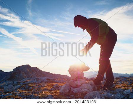 Man Put The Last Stone Intopeak Of  Pyramid. Balanced Stone Pyramid On  Mountain Summit