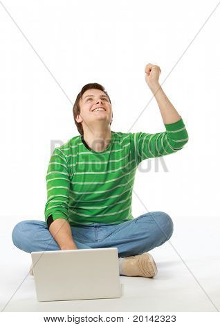 A happy young man sitting on the floor with a laptop