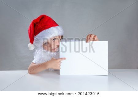 Little Santa Peeping From Behind A White Envelope And Shows It. Sitting Behind A White Table Looking