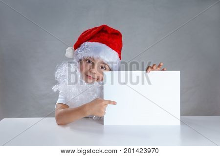 Little Santa Holding A White Envelope And Shows Him Smiling. Sitting Behind A White Table Looking At