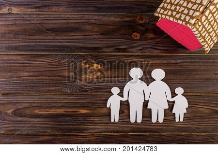 Happy paper family with house on dark vintage wooden background