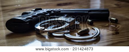 Closeup Of Silver Handcuffs With Golden Bullet Shells With Gun Pistol On A Wooden Background Used By
