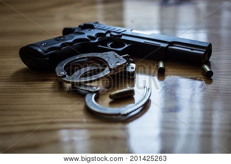 Black Pistol Gun With Silver Handcuffs And Golden Bullet Shells Laying On A Wooden Background For Fi