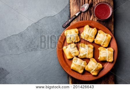 Mini chilean empanadas on clay plate with typical chilean drink vino con harina - red wine with toasted flour.