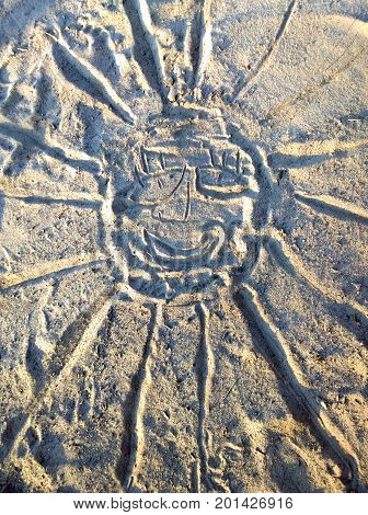Children's drawing on the sand in the form of a smiling sun with divergent rays