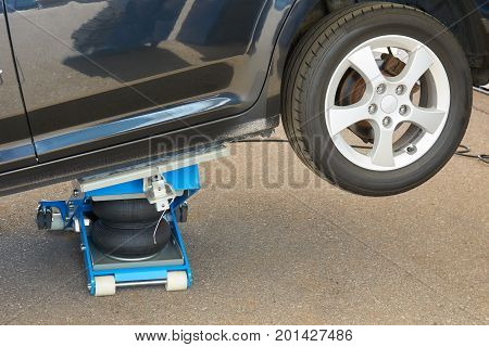 Car is raised by pneumatic jack for tire fitting