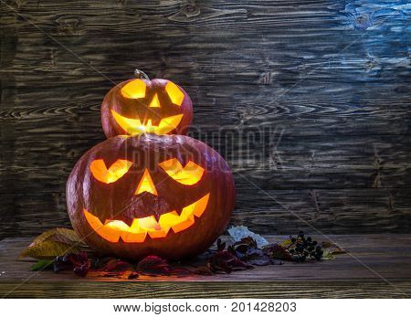 Grinning pumpkin latern or jack-o'-lantern is one of the symbols of Halloween. Halloween attribute. Wooden background.