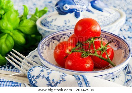 Fresh tomatoes in bowl at the table in blue crockery with basil