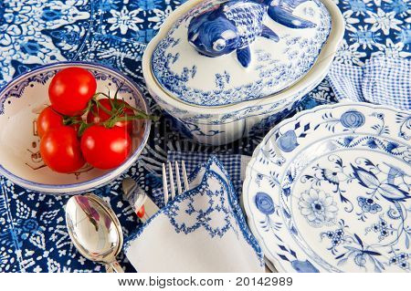 Fresh tomatoes in bowl at the table in blue crockery
