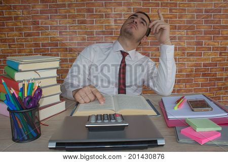 young business man at the office is reading an interesting book out of his stack. man reading book with textbook stack on wooden desk