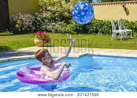 A teenage boy in a pink inflatable ring catching a ball in a swimming pool