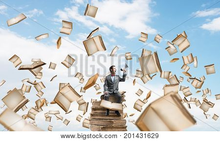 Young businessman sitting on book and screaming emotionally in megaphone