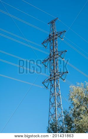 High voltage electrical power line pylon with blue sky as background on a sunny day