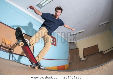 Skateboarder performing a blunt to fakie on a mini ramp at indoor skate park.