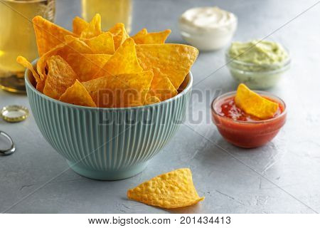 Crunchy Nachos In Blue Bowl On Table With Dip Sauces And Beer.