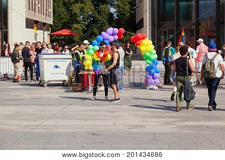 SOUTHAMPTON UK - August 26 2017: Southampton Pride 2017 City's second annual Pride event in Southampton UK. Two men talking at the entrance with a rainbow balloon arch behind them.