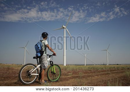 A young man on a bicycle rides past a wind power plant.